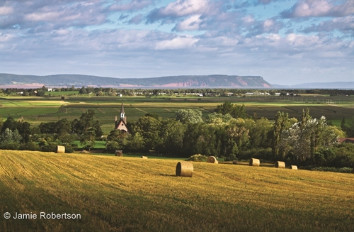 This is beautiful Grand Pré with the Bay of Fundy and Cape Blomidon in the background.  A gorgeous spot in Nova Scotia.